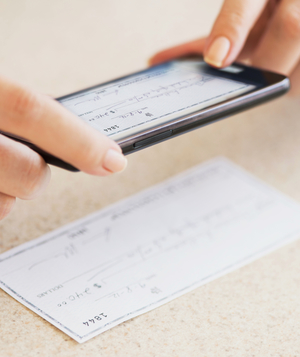 Woman taking photo of check with smartphone