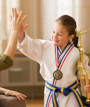 Girl with karate trophy hi-fives mother