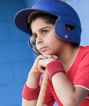 Boy in baseball uniform looking sad
