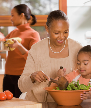Grandmother helps granddaughter with salad