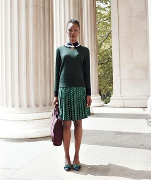 Model wearing green sweater and pleated skirt