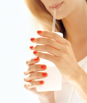 Model wearing bright orange nail polish