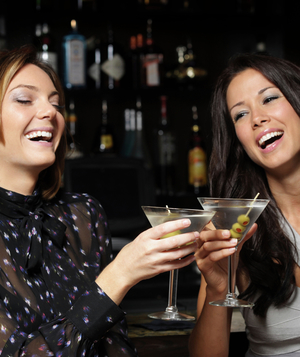 Women drinking martinis at bar