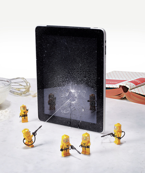 Little hazmat men cleaning a digital tablet