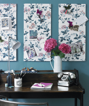 Desk with floral patterned pin boards on the wall over it