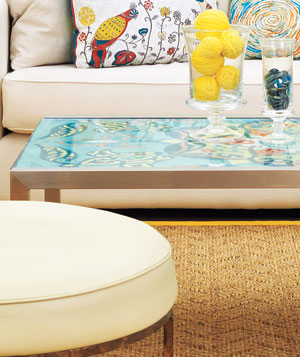 Glass coffee table with colorful fabric under it