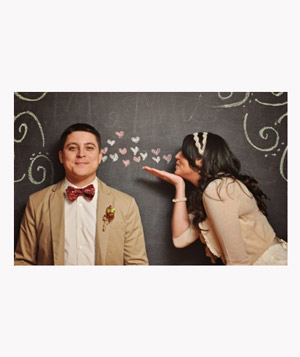 Couple in front of chalkboard in wedding photobooth