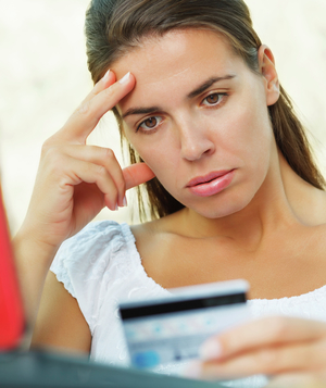 Woman looking at credit card, worried