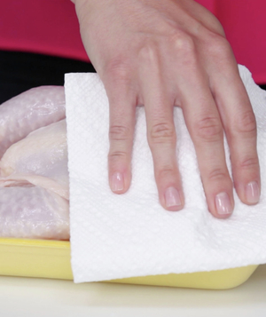 Patting raw chicken with paper towel
