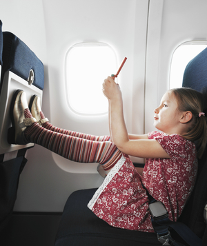Little girl with feet on plane seat