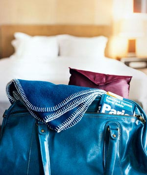 Blue carry-on bag at the foot of a hotel bed