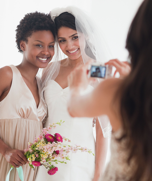 Woman taking photo of bride and bridesmaid