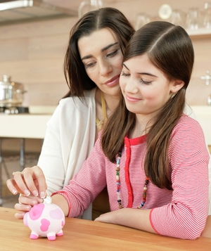Mother and daughter putting money in piggy bank