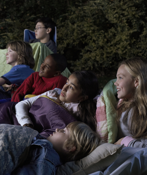 Children watching movie in backyard