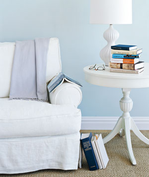 White chair with a side table of books