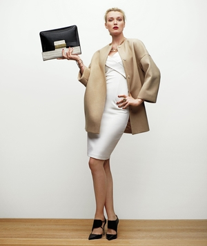 Model wearing structured camel coat and white dress