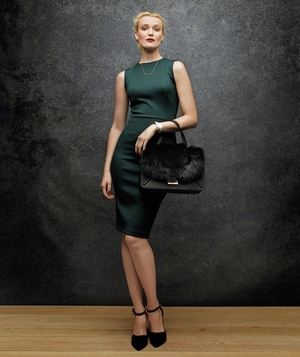 Model wearing neoprene dress and carrying statement satchel
