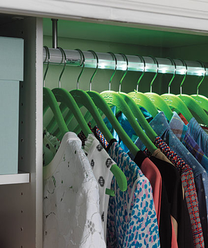 LED closet rod shown with clothes on green hangers