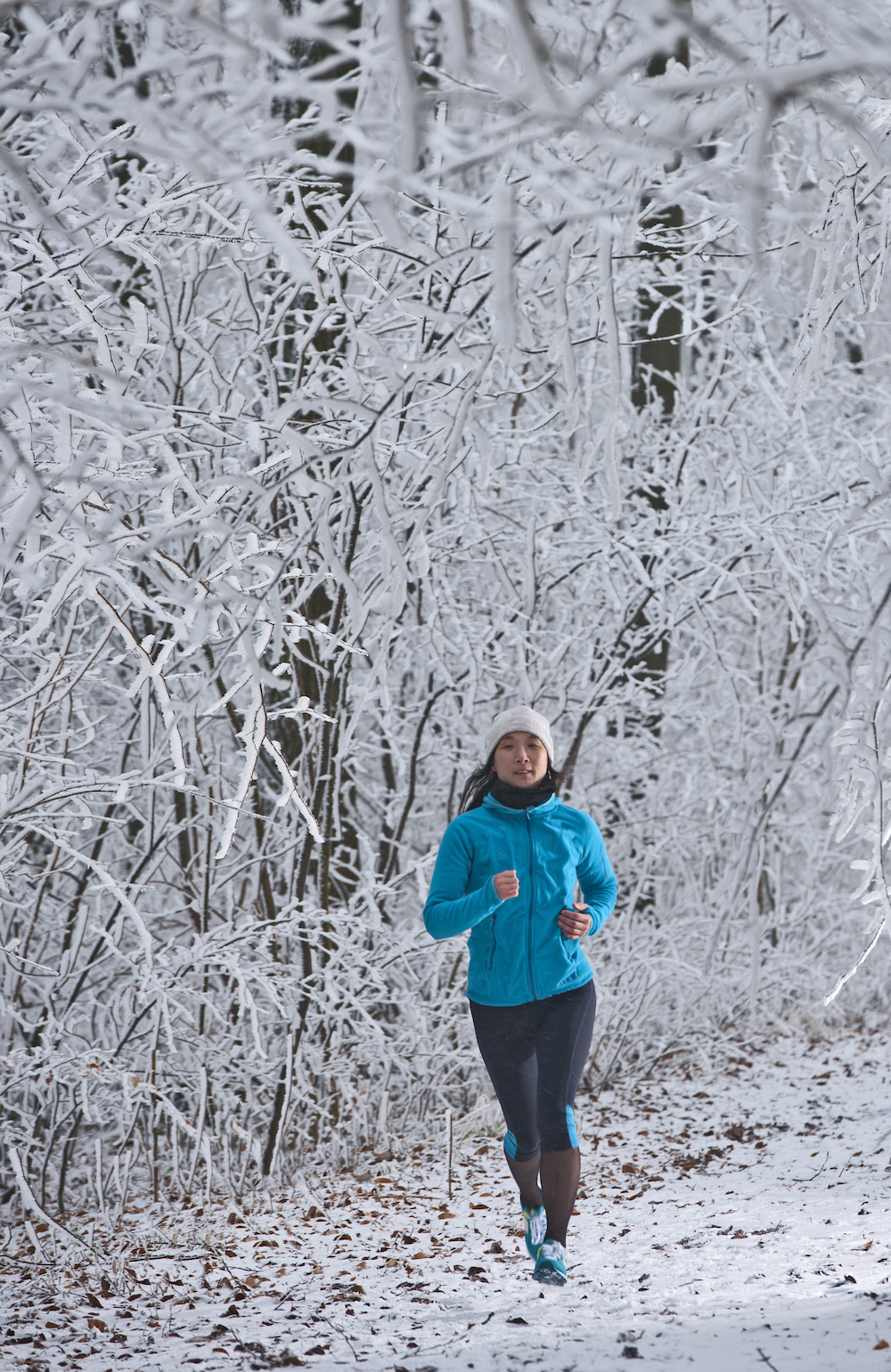woman running outside in winter in snowy trees