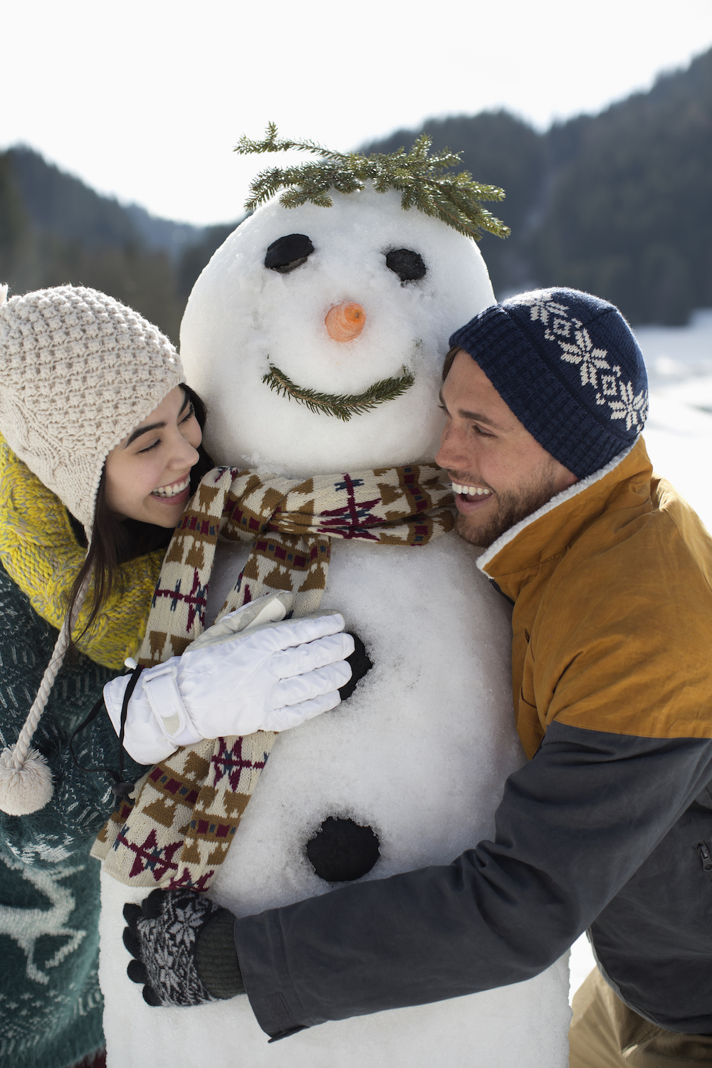 couple smiling with snowman in winter