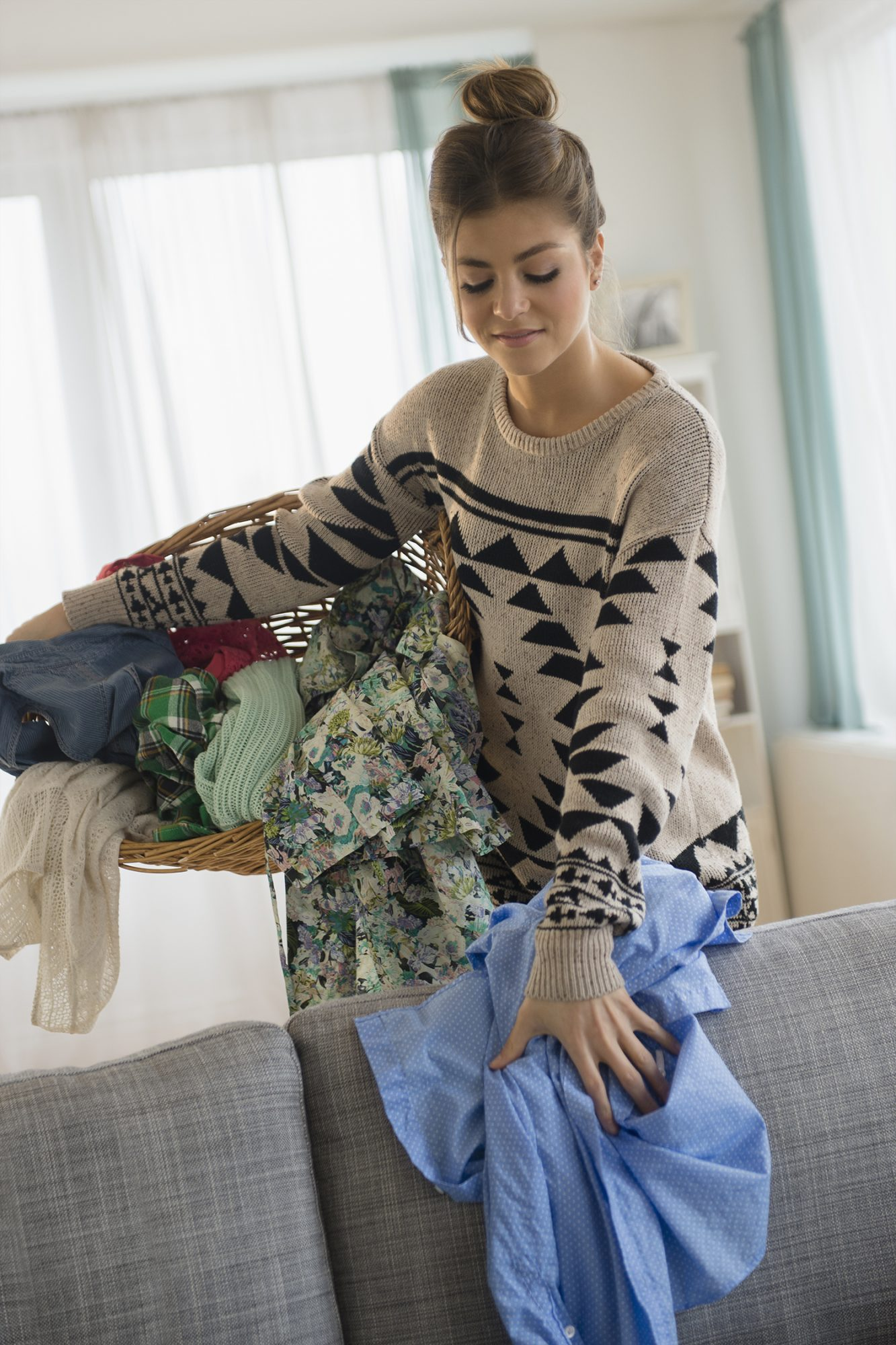Woman Doing Her Laundry and Smiling While Picking Up Clothes