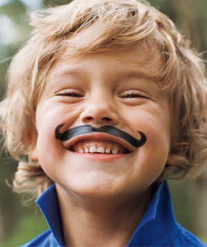 Portrait of  grinning blonde boy with painted-on thick black mustache