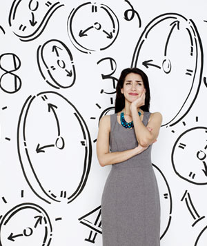 Worried woman in front of clock wall