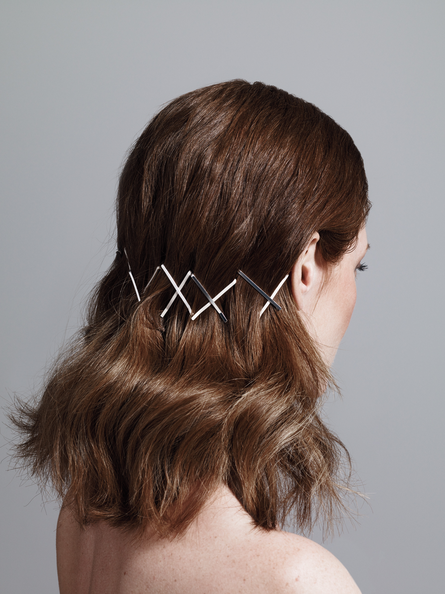 Model with criss cross bobby pins in back of hair