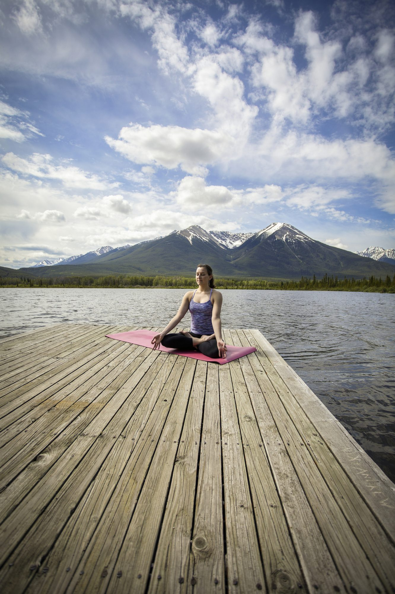 woman meditating on dock in mountains