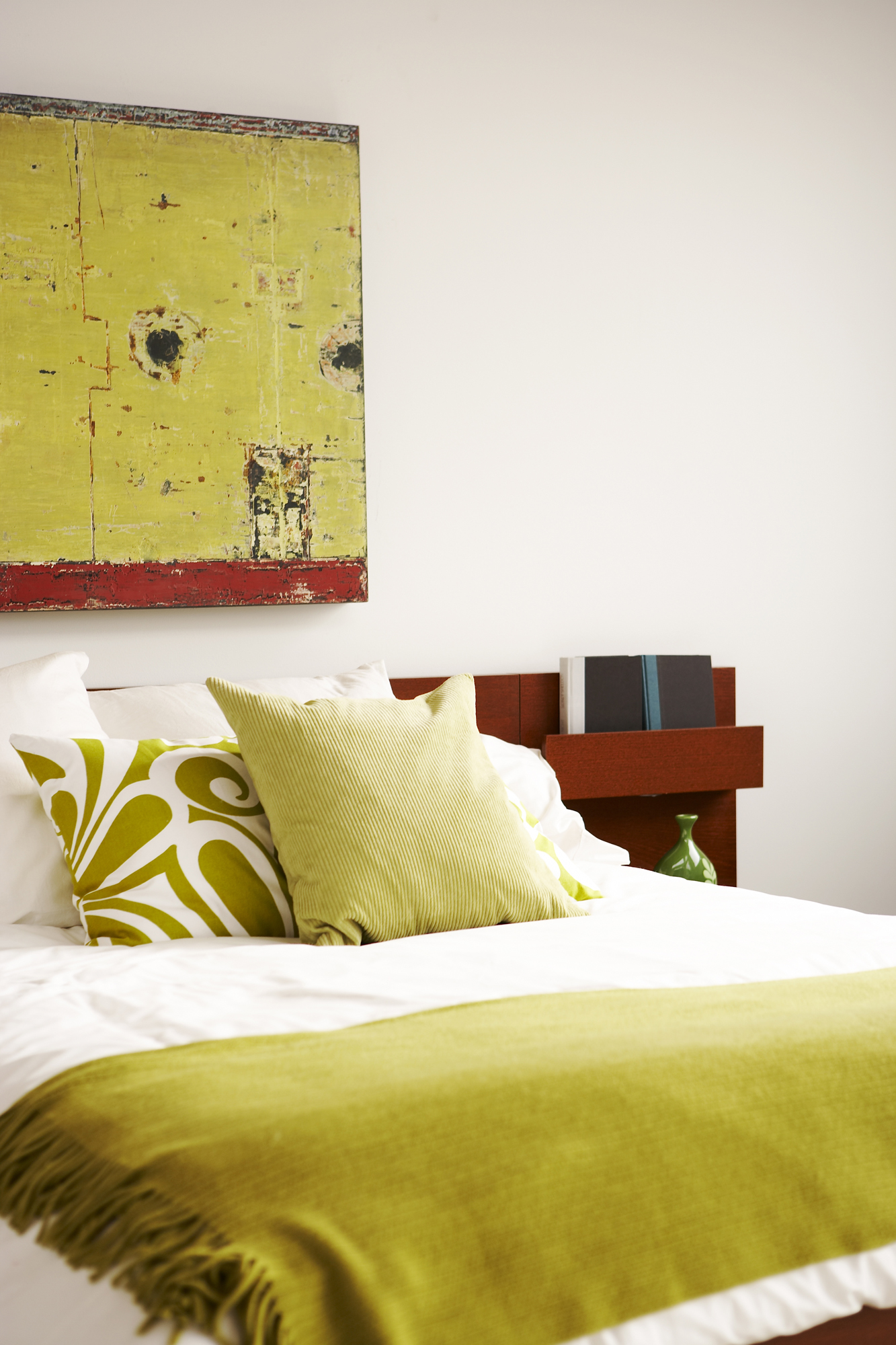 Bedroom with chartreuse details and art on wall