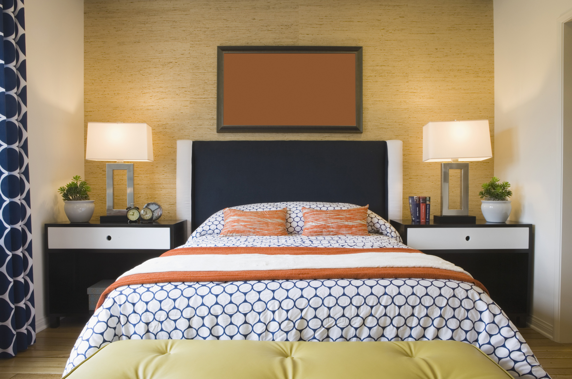 Bed with wicker headboard and blue and orange bedding