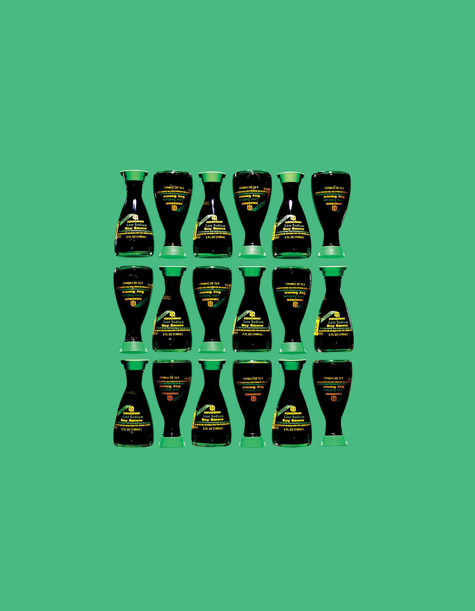 Soy sauce bottles lined up on green background