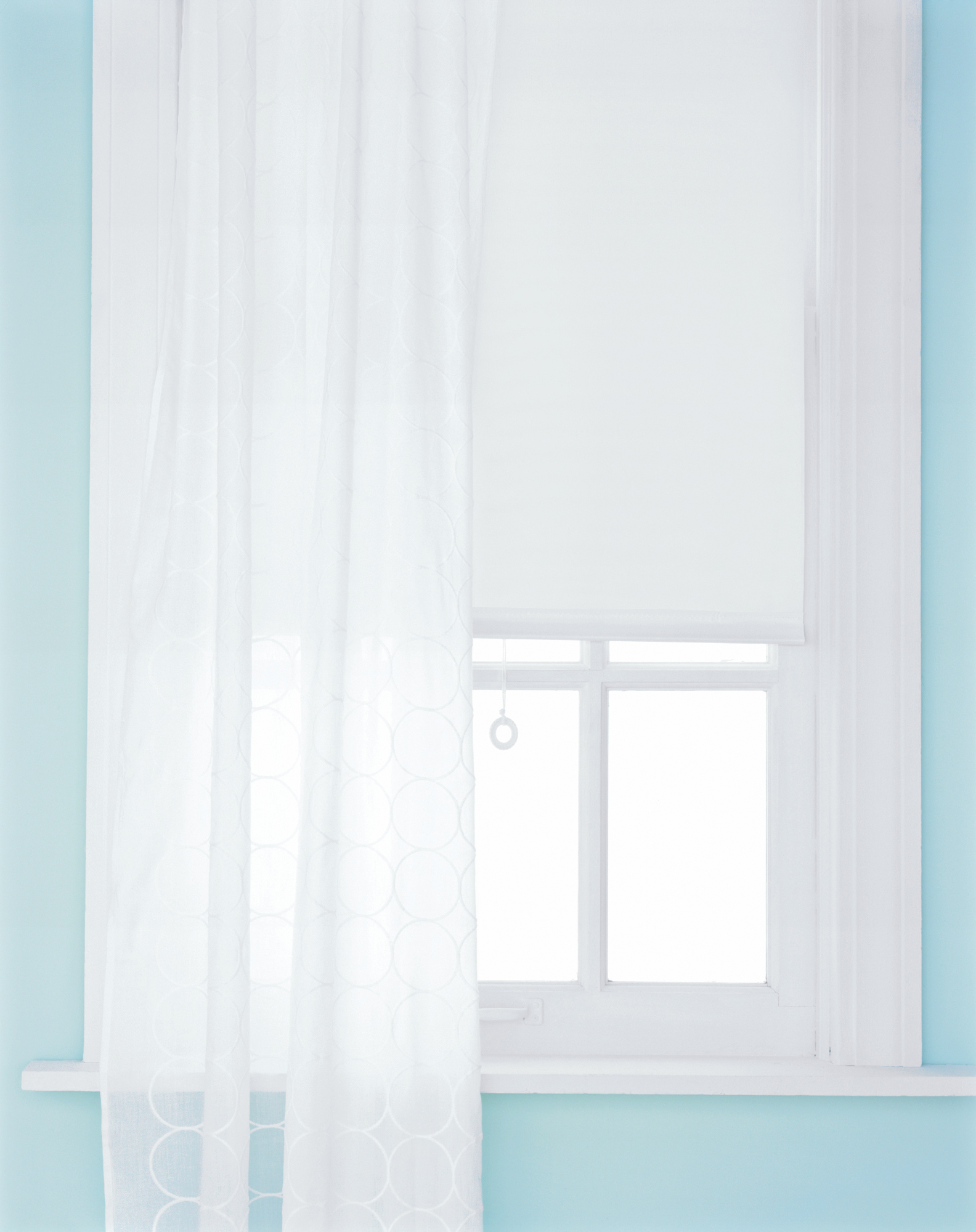 Window with white shade and sheer curtain
