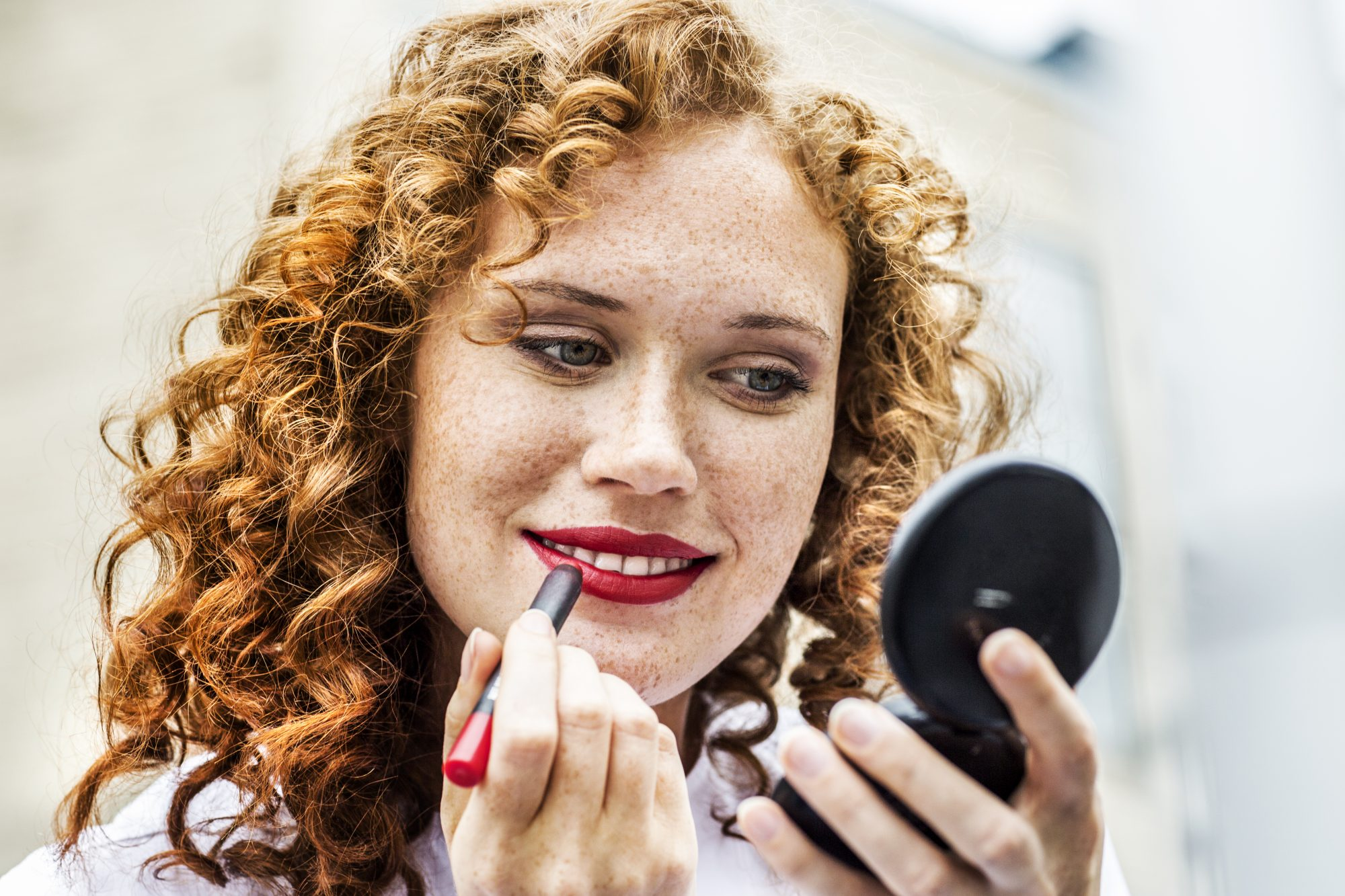 girl putting on lipstick