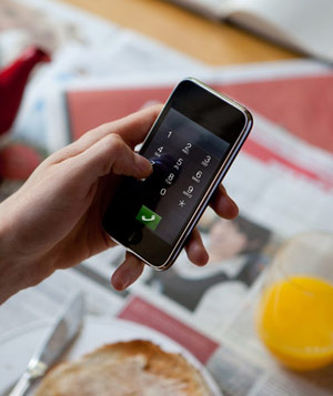 Hand using smartphone at breakfast table