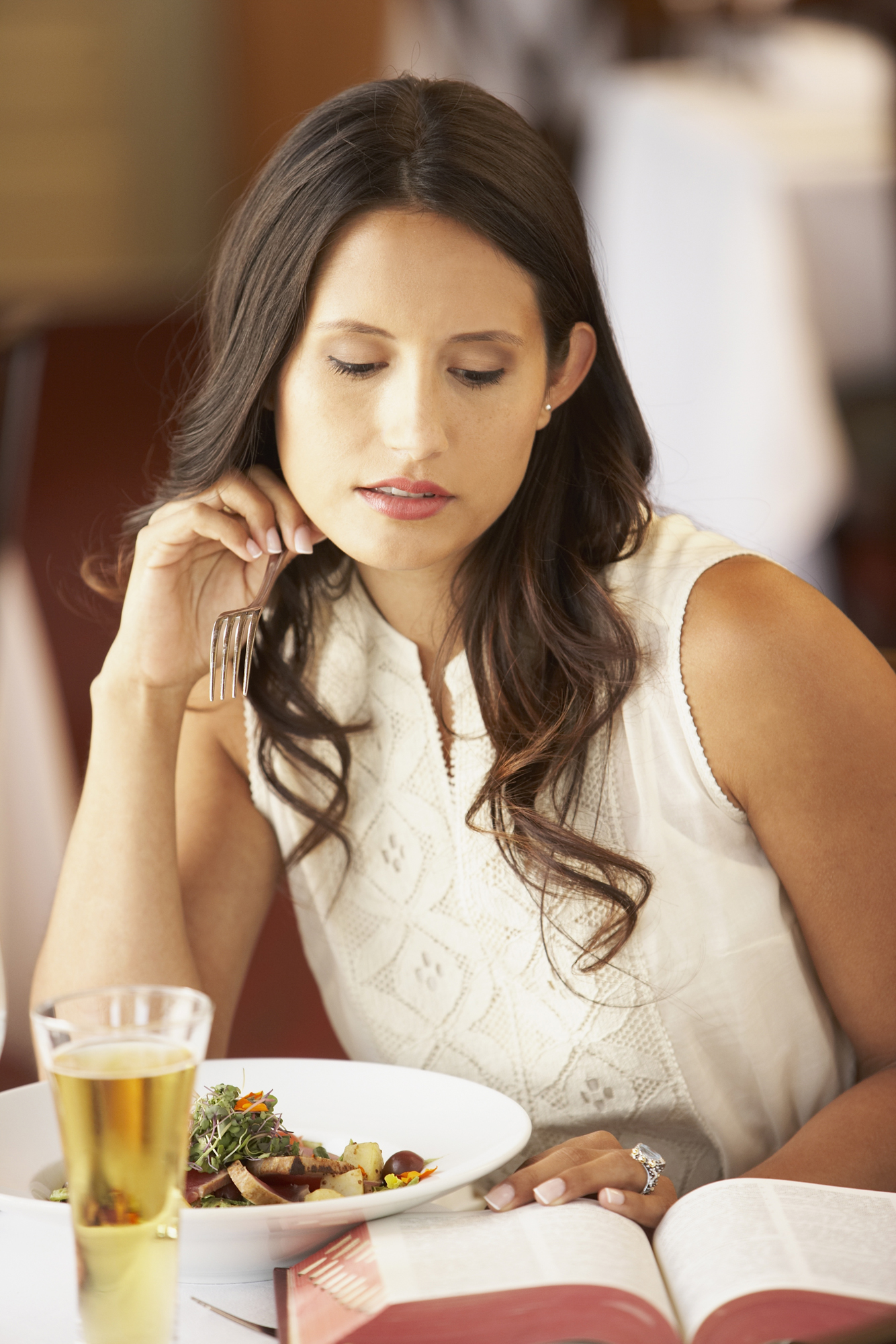 Woman at restaurant with book