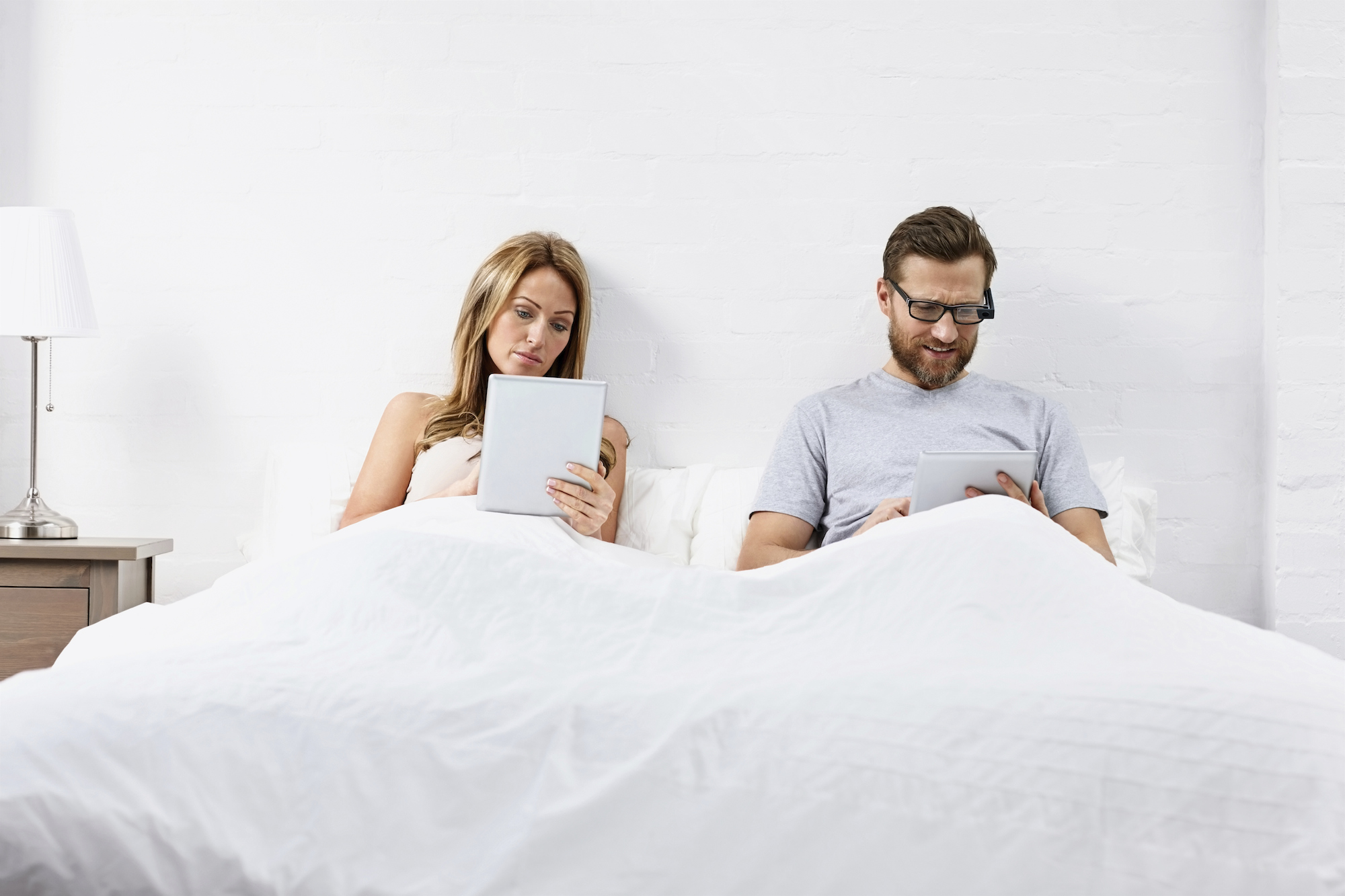 Couple in bed on their phones.