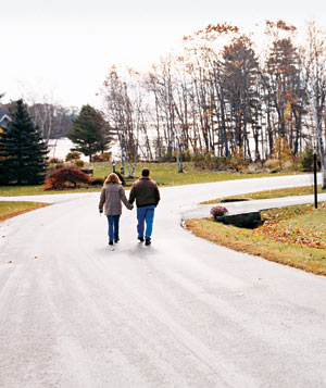 Couple walking down a road holding hands