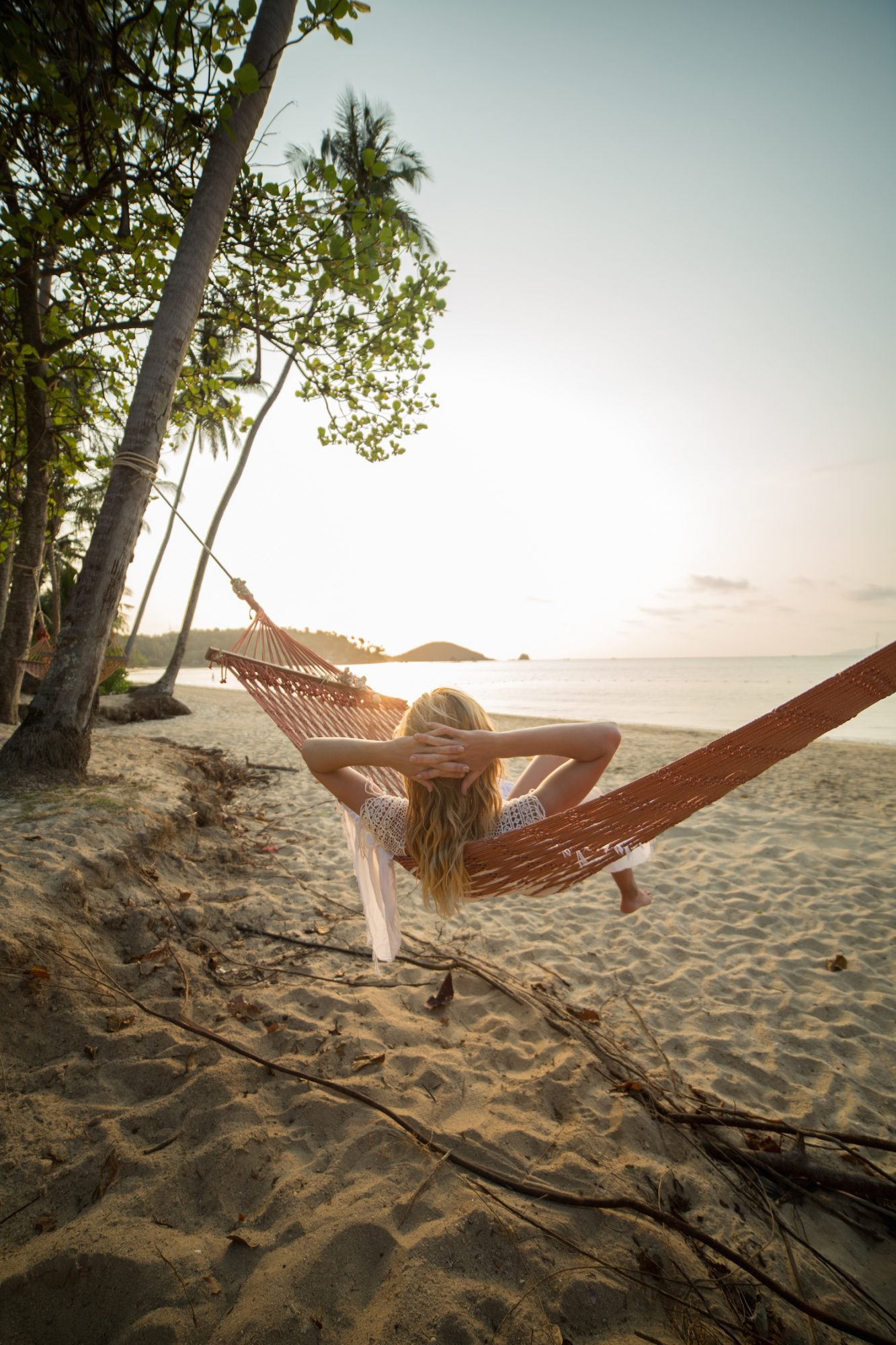 Woman on tropical beach lying down on hammock