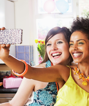 Women taking photo of themselves with smartphone