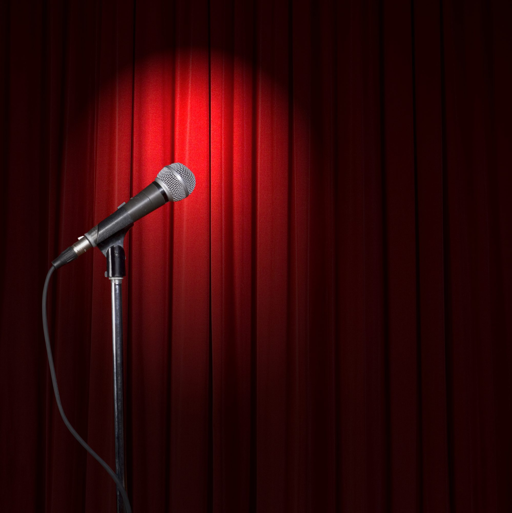 Spotlight on microphone and red curtain