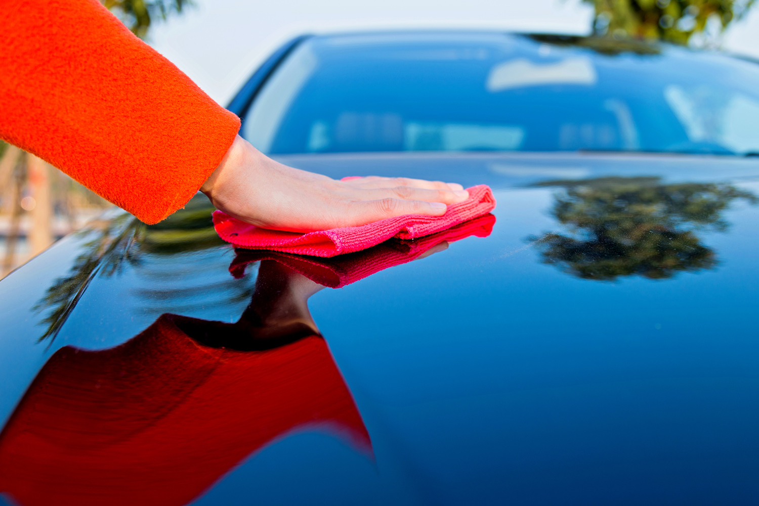Woman polishing car with cloth