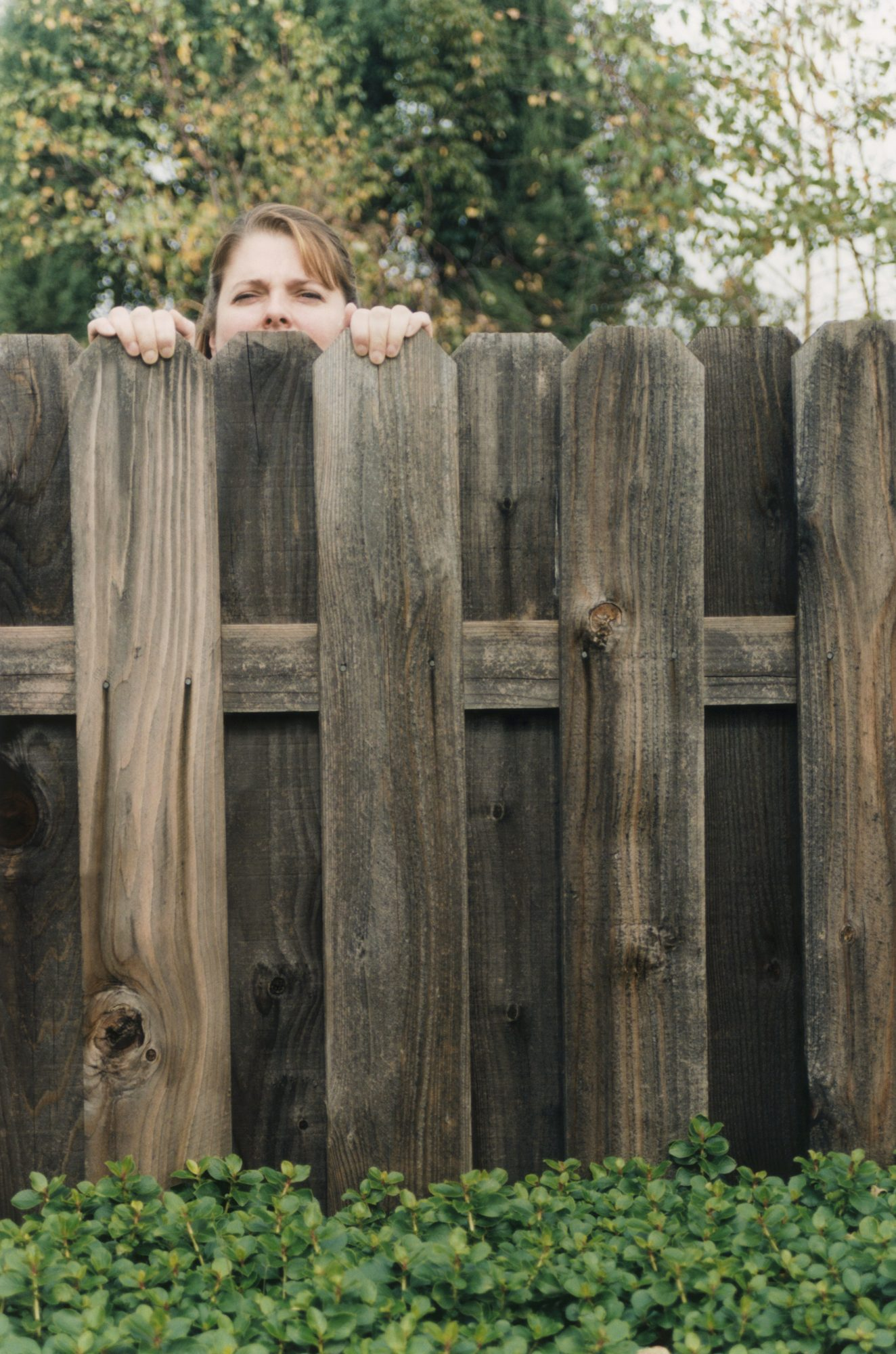 Woman peering over fence
