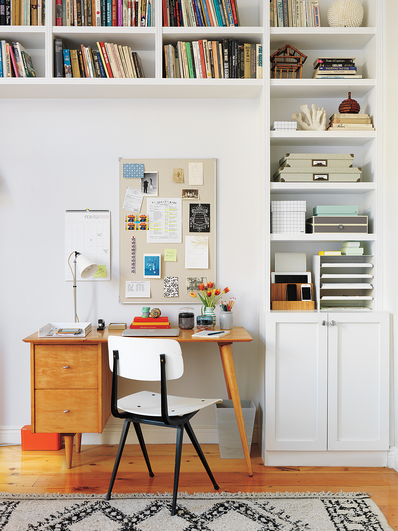 Desk with white chair, bulletin board, wall-shelving