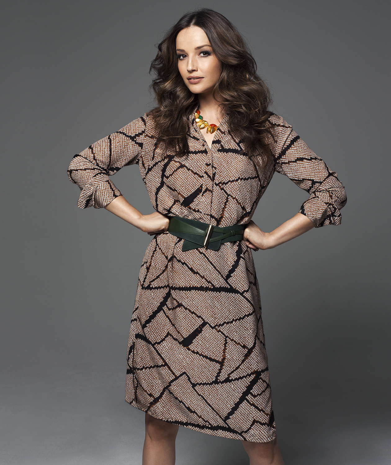 Model wearing brown patterned dress with green belt