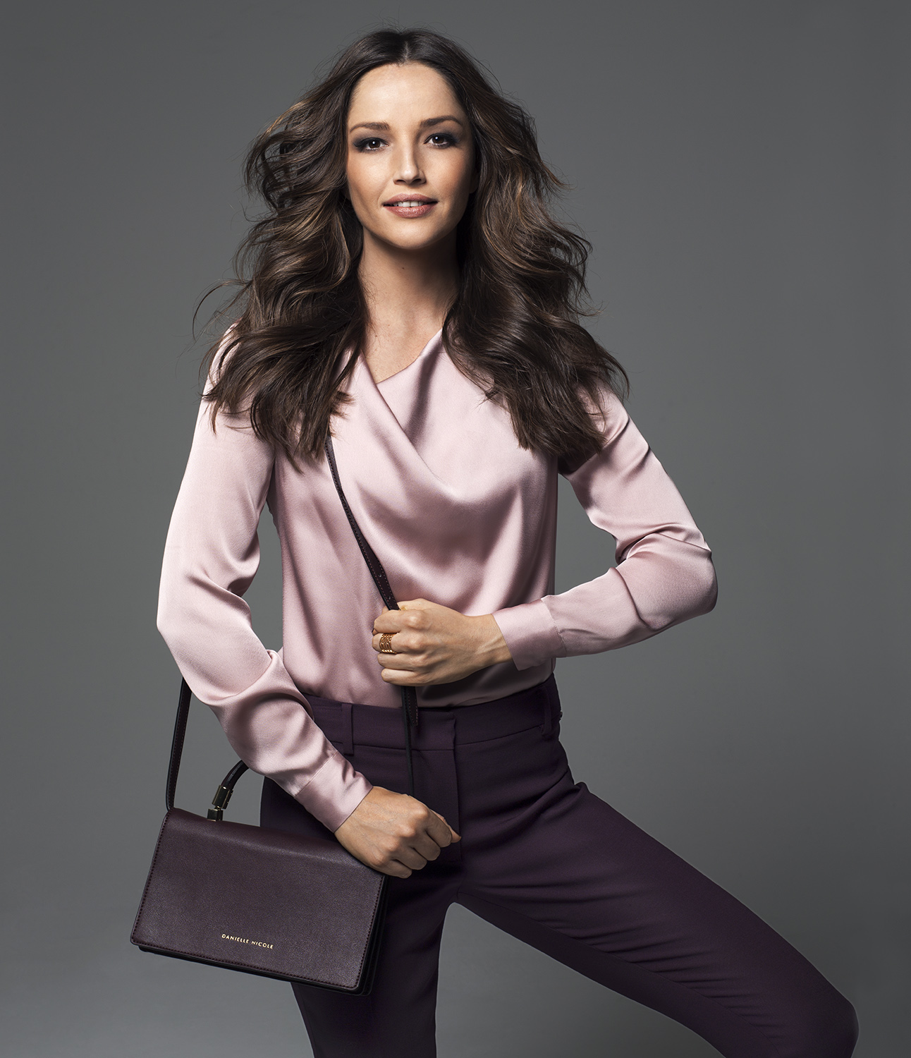 Model wearing pink blouse and eggplant pants