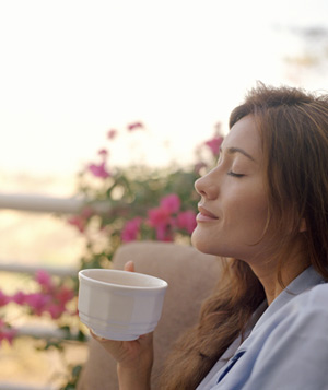 Woman drinking coffee on deck near flowers