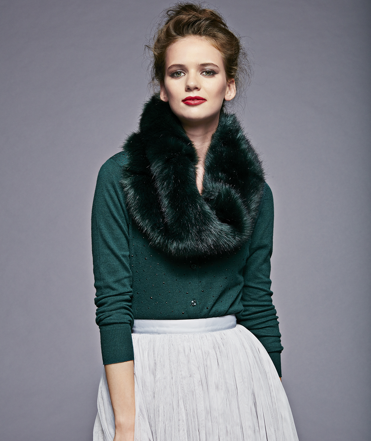 Model with green faux fur stole and cardigan