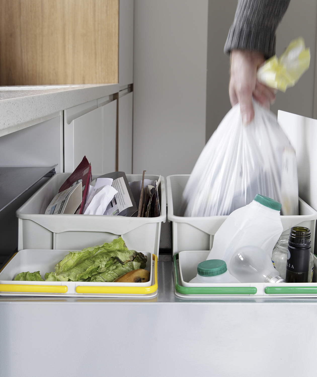 Person removing trash bag from waste and recycling drawer