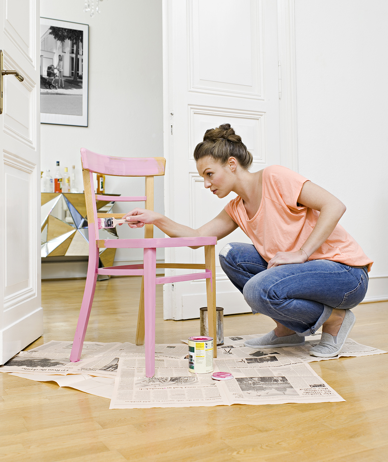 Woman painting wooden chair